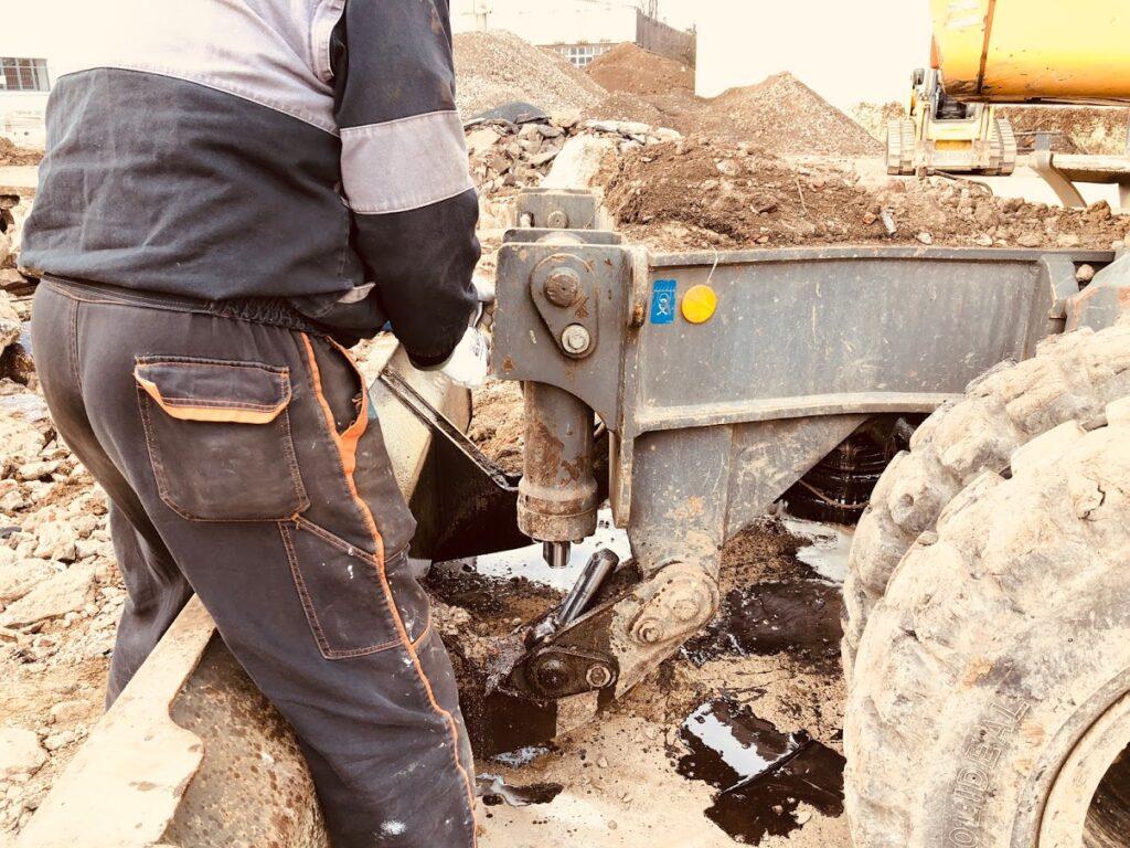 Nepozorný strojník sevřel kus betonu mezi hrablo a pístnici